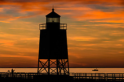 The South Pier Lighthouse in Charlevoix, Michigan, is a favorite spot for tourists and residents wanting to catch a dramatic sunset. The lighthouse, located on Lake Michigan sits at the entrance of the Pine River Channel which provides access to Round Lake and Lake Charlevoix. The current 41-foot steel structure was built in 1941. From 1885 to 1914 the light was located on a wooden tower on the north pier. In 2005, the U.S. Coast Guard deemed the light as no longer needed and in 2008 transferred the Charlevoix South Pier Lighthouse to the City of Charlevoix under the National Historic Lighthouse Preservation Act.