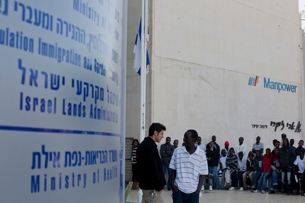 "A guard is avoiding from a Sudanese refugees to enter the Immigration and Borders Authority as others wait outside to receive a visa in the city of Eilat on  February 27 2011. The municipality hung 1,500 red flags around the city as a sign of warning and put up hundreds of banners reading: ""Protecting our home, the residents of Eilat are drawing the line on infiltration."" Eilat Mayor Meir Yitzhak Halevi said that 10 percent of the city's population was currently made up of migrants and that the residents feel that the city has been conquered...Photo by Olivier Fitoussi."