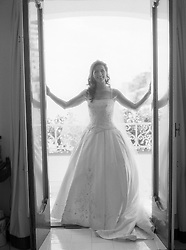 Bride on a balcony about to enter a room