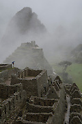 Early morning visitor viewing ancient Inca settlement of Machu Picchu through the misty clouds