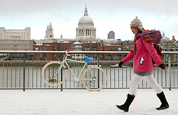 © under license to London News Pictures. 2010.12.17 A woman walks  along the South Bank of the River Thames opposite St Pauls Cathedral. Snow hits London again this afternoon (Fri) with freezing temperatures and blizzard conditions .Picture credit should read Carmen Valino/London News Pictures...