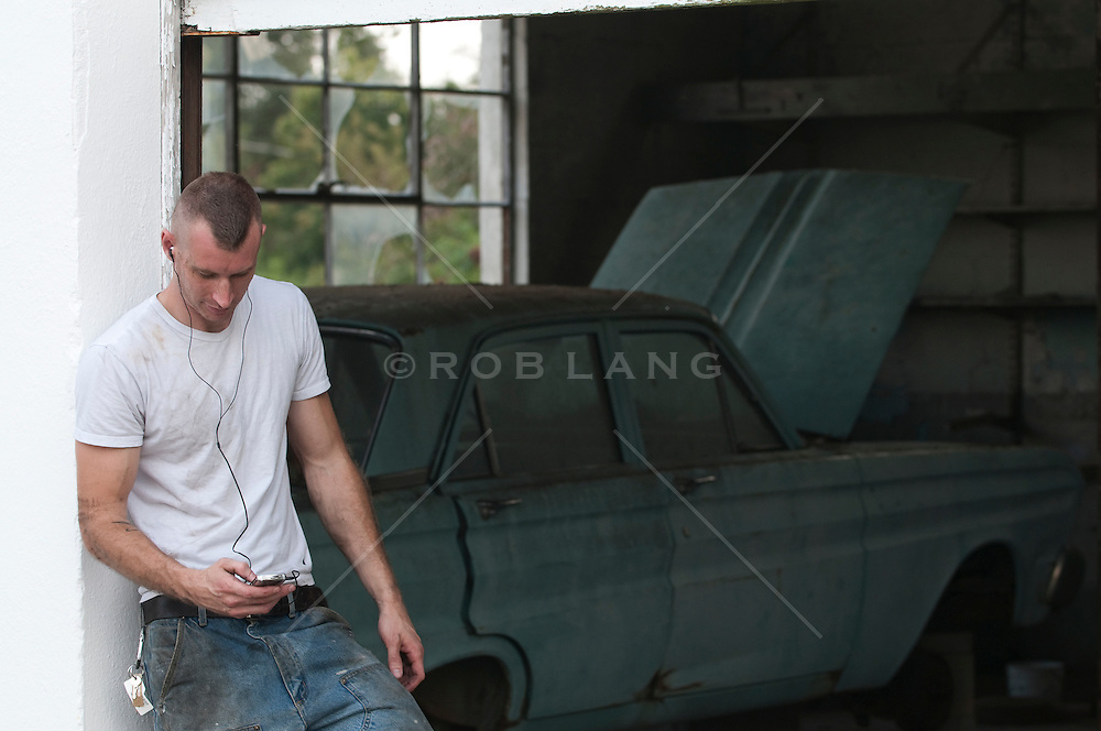man with head set on dialing his phone by an old car in a garage