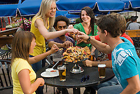 A group of young adults enjoy beer and lunch on the outdoor patio of Merlins Restaurant, at the base of Blackcomb Mountain in Whistler, BC Canada