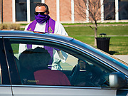 "05 APRIL 2020 - DES MOINES, IOWA:  Rev. RUSSELL LACKEY follows ""Social Distancing"" guidelines while he talks to parishioners during a drive through Palm Sunday service sponsored by Luther Memorial Church on the campus of Grand View University in Des Moines. About 150 people attended the service. They remained in their cars while the ministers read a short passage from the Bible, handed out palms and blessed them. On Sunday, 05 April, Iowa reported 868 confirmed cases of the Novel Coronavirus (SARS-CoV-2) and COVID-19. There have been 22 deaths attributed to COVID-19 in Iowa. Restaurants, bars, movie theaters, places that draw crowds are closed until 30 April. The Governor has not ordered ""shelter in place"" but several Mayors, including the Mayor of Des Moines, have asked residents to stay in their homes for all but essential needs. People are being encouraged to practice ""social distancing"" and many businesses are requiring or encouraging employees to telecommute.        PHOTO BY JACK KURTZ"