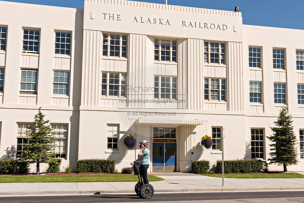 A woman rides a Segway past the Alaska Railroad depot in downtown Anchorage, Alaska.  The Moderne-style railroad station was built in 1942 and is the starting point of the Denali Star luxury train.