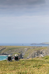 Two people relaxing on the clifftop at Carnewas on the North Cornwall coast.