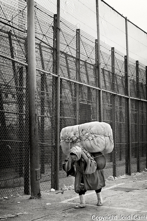 MELILLA, SPAIN - APRIL 21, 2010 : A woman porter passing  next to the separation fence between Spain and Morocco at the  border of El Barrio Chino, where the porters  have to push or carry contraband packages that weigh 80 to 100 kg. on April 21 , 2010 in Melilla. Spain. Every day at the pedestrian border of El Barrio Chino hundreds of people are involved in transporting smuggled goods from Melilla a Spanish enclave on the North African coast to Morocco.For each package introduced in morocco receive between 3 an 5 euros depending on size,with a little luck achieved make three trips a day.It is estimated that from Monday to Thursday on foot enter Melilla 8.000 porters, mostly women, to return to Morocco with huge sacks of goods from the warehouse border area of Beni Enzar in Melilla .( Photo by Jordi Cami )