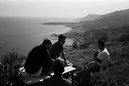 A group of refugees rest on some chairs and tables normaly uses by hunters before continuing their journey to France. In the backgrund the towns of Menton and Monaco. Federico Scoppa