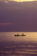 Lovina, Bali 1993.  Two boys take a sunset paddle in their canoe and are silhouetted by the shimmering sea.