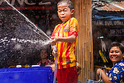 13 APRIL 2014 - BANGKOK, THAILAND: A Thai child uses a hose to squirt tourists on Khao San Road, Bangkok's backpacker district, during Songkran water fights. Songkran is celebrated in Thailand as the traditional New Year's Day from 13 to 16 April. Songkran is in the hottest time of the year in Thailand, at the end of the dry season and provides an excuse for people to cool off in friendly water fights that take place throughout the country. Songkran has been a national holiday since 1940, when Thailand moved the first day of the year to January 1.    PHOTO BY JACK KURTZ
