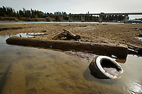 JEROME A. POLLOS/Press..An old tire rests in the silt of the Spokane River as the water recedes to about 50 percent of normal Friday, according to the latest report by the Natural Resources Conservation Service. With the season's low snowpack, runoff will be below normal across the state and irrigation water shortages may occur.