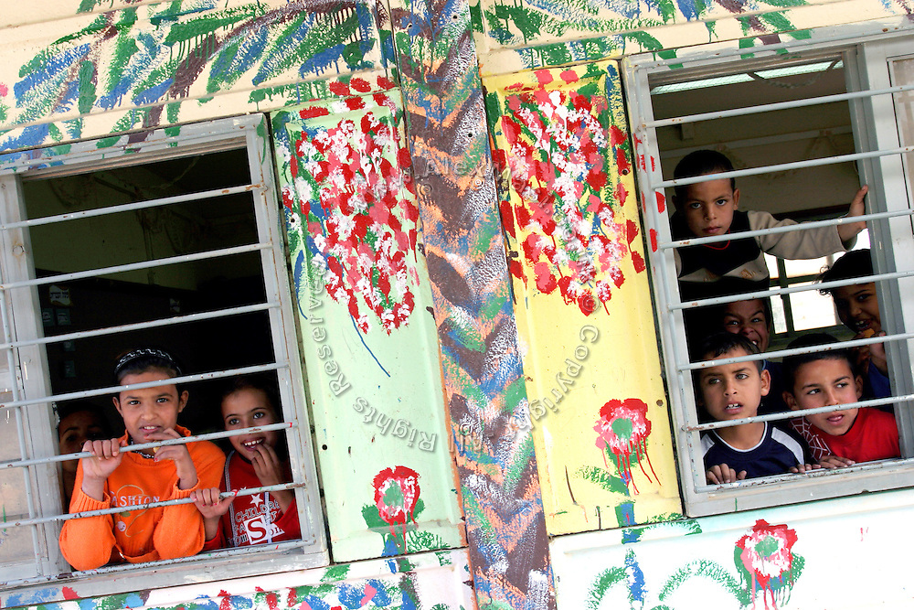 Bedouin children are looking outside from a window of a classrooom in the unrecognised village of Abu Tlul, in the Negev Region of Israel. Numbering around 200.000 in Israel, the Bedouins constitute the native ethnic group of these areas, they farm, grow wheat, olives and live in complete self sufficiency. Many of them were in these lands long before the Israeli State was created and their traditional lifestyle is now threatened by subtle Governmental policies. The seven Bedouin towns already built are all between the 10 more impoverished towns in Israel..