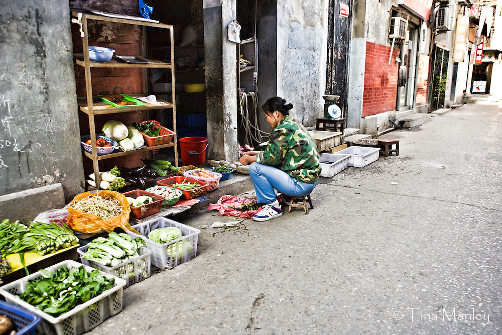 CHINA, WUHAN:  Street scene in Wuhan alley with vegetables displayed on the street outside a tiny produce shop and a woman cleaning greens. Photo Illustration.