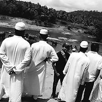 PINNAWELA, OCTOBER-3 : muslim students watch an elephant herd bathing in the Ma Oya river in Pinnawala, October 3, 2005, Sri Lanka.  PINNAWELA, OCTOBER-3 : an elephant greets a visitor   in Pinnawela, October 3, 2005, Sri Lanka.   .The Pinnawela orphanage was started in 1975 and initially designed to afford care and protection to the many baby elephants found in the jungle without their mothers. In most cases the mother either had died or been killed. .Animals are allowed to roam freely duringthe day and a herd structure allows to form. there are only a few elephant orphanges worldwide. At Pinnawela an attempt was made to simulate, in a limited way, the conditions in the wild. Currently the herd consists of 75 elephants under the surveillance of legendary  Mahout chief Sumanabanda.