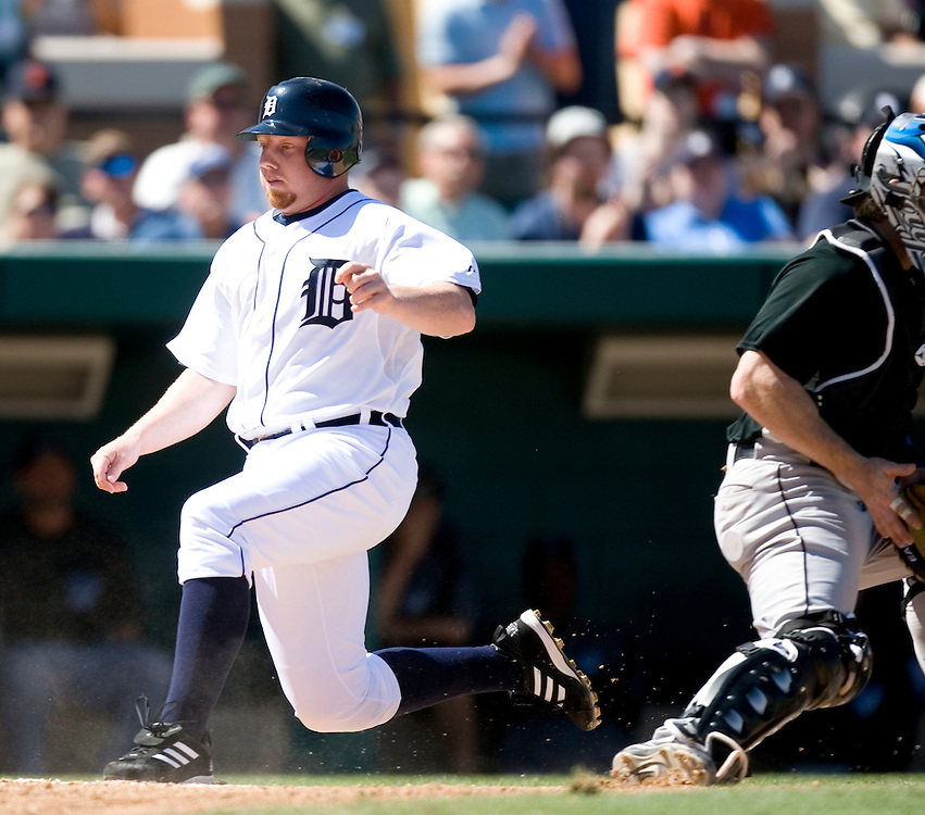 Detroit Tigers' Chris Shelton (L) runs past Toronto Blue Jays catcher Gregg Zaun to score on a single by the Tigers' Placido Polanco during the third inning of their MLB spring training baseball game in Lakeland, Florida March 6, 2007.  REUTERS/Scott Audette(UNITED STATES)