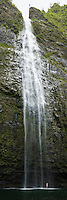 A man standing underneath Hanakapi'ai Falls in the Hanakapi'ai Valley on the Na Pali Coast of Kauai, Hawaii.