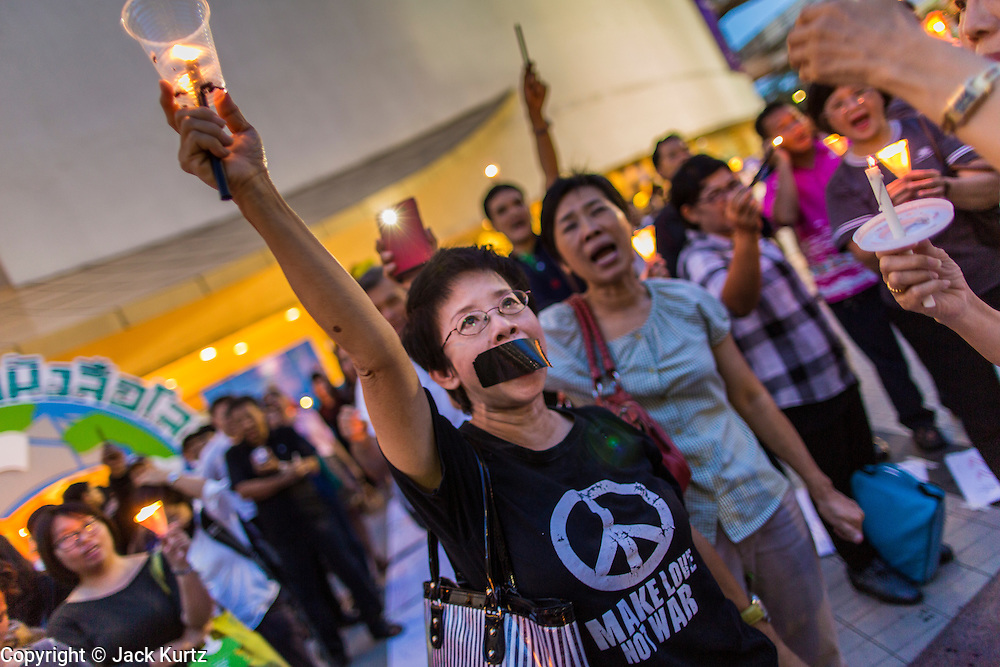 20 MAY 2014 - BANGKOK, THAILAND: A Thai woman holds up a candle during a vigil against martial law. About 200 Thais gathered at the Bangkok Art and Culture Centre in central Bangkok to protest the army's decision to impose martial law.   PHOTO BY JACK KURTZ