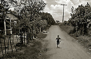 San Pedro de Macorís, Dominican Republic- A youngster runs along one of the small dirt roads leading into the sugarcane plantations and the worker communities known as bateyes. (Photo by Robert Falcetti)