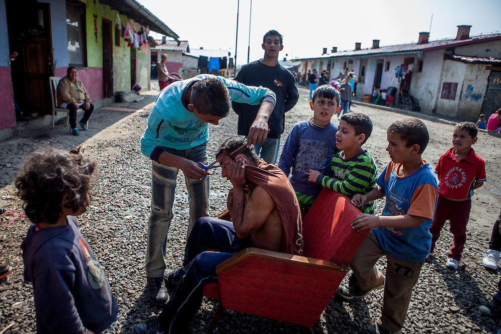 "One inhabitant of the Roma settlement in Moldava nad Bodvou is getting a haircut outside on the main road of the settlement. ""Budulovskej Street"" is a segregated Roma settlement which is located about 2 km behind the Slovak village of Moldava nad Bodvou."