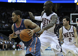 Apr 11; Newark, NJ, USA; Charlotte Bobcats point guard D.J. Augustin (14) drives to the basket past New Jersey Nets small forward Travis Outlaw (21) during the second half at the Prudential Center. The Bobcats defeated the Nets 105-103.