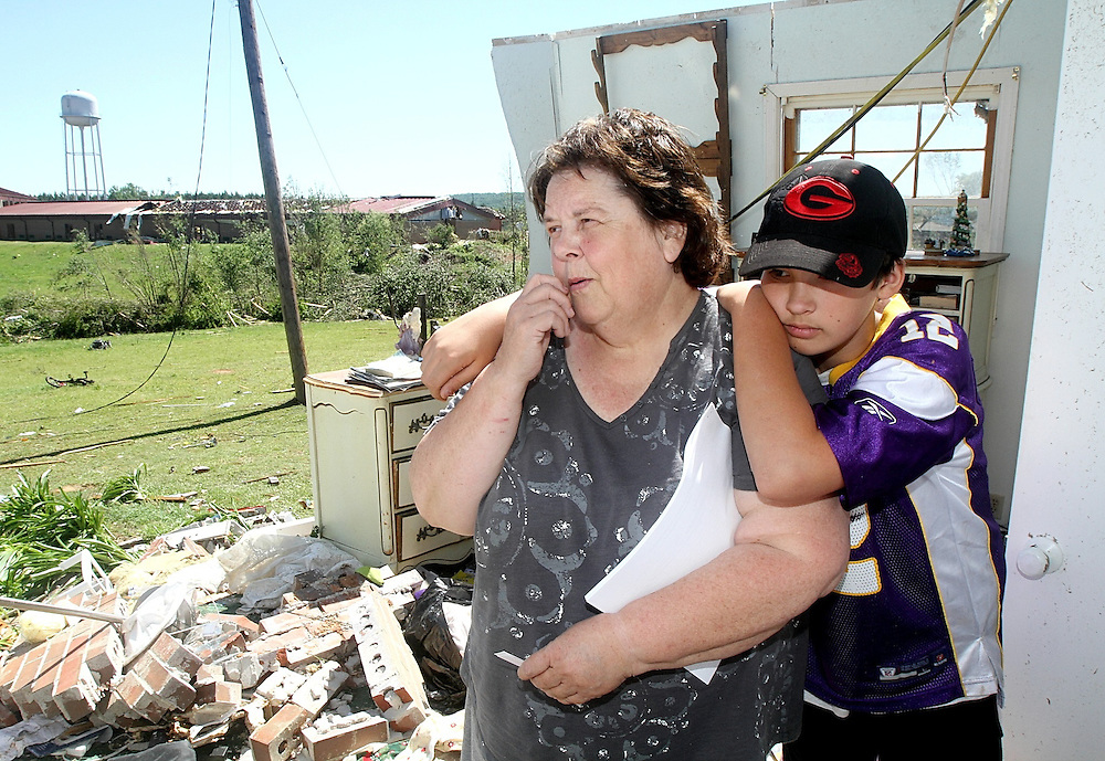Linda Moncrief stands in what is left of her master bedroom surveying the damage with her grandson Tyler Jordan, age 11, after a suspected tornado hit her home near Manchester South of Atlanta last night.