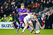 Portsmouth midfielder Ronan Curtis (11) tussles with Milton Keynes Dons midfielder Jordan Houghton (24) during the EFL Sky Bet League 1 match between Milton Keynes Dons and Portsmouth at Stadium MK, Milton Keynes, England on 29 December 2019.
