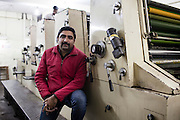 Mohit Bhargava, the printing company owner, poses for a portrait in front of one of his printing machines in his printing workshop that prints the Khabar Lahariya weekly newspaper in Allahabad, Uttar Pradesh, India on 06 December 2012. Photo by Suzanne Lee / Marie Claire France