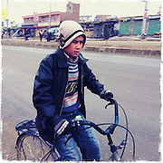A boy rides his bicycle in a Hazara neighborhood near Dar ul Aman Palace.