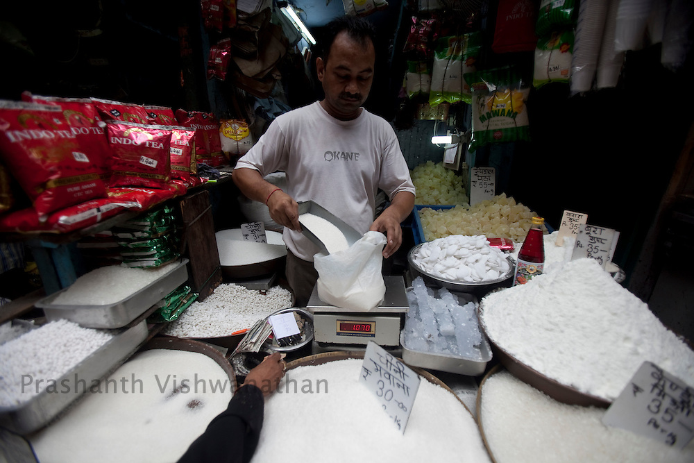 A shopkeeper weighs sugar, as he sells different varities of sugar at the busy wholesale market of Old Delhi, in New Delhi, India, on Wednesday September 2, 2010. Photographer: Prashanth Vishwanathan/Bloomberg News