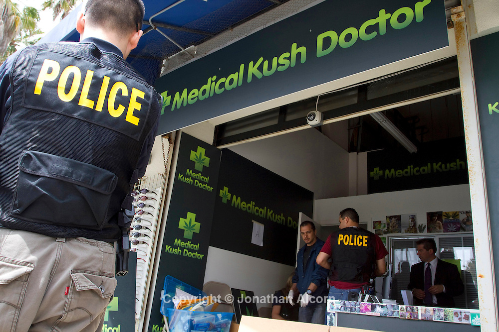 Police Investigators conduct an investigation while serving a search warrant at the Medical Kush Doctor, a medical marijuana dispensary on Ocean Front Walk in Venice Beach. The woman declined to give any information..©Jonathan Alcorn 2011
