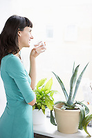 Businesswoman smiling drinking and looking through window by pot plant