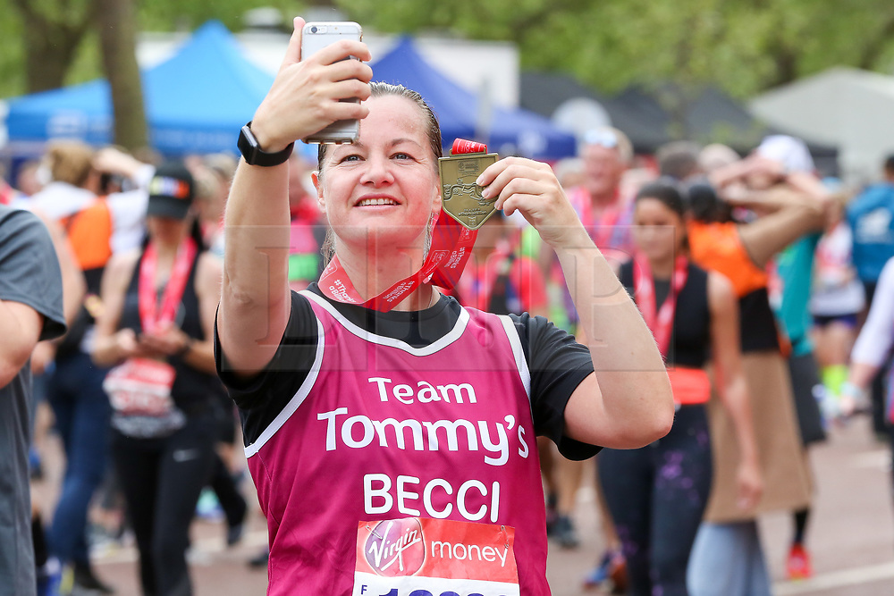 © Licensed to London News Pictures. 28/04/2019. London, UK. A runner takes a selfie after completing the 2019 Virgin Money London Marathon. Photo credit: Dinendra Haria/LNP