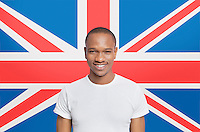 Portrait of young man in white t-shirt smiling against British flag