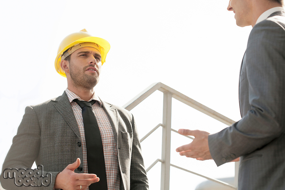 Two young male engineers discussing on stairway against clear sky