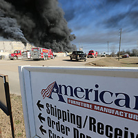 Heavy black smoke fills the air as fire crews move to the south end of American Furniture in an attempt to stop the fire from spreading any more Friday morning.