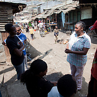 Residents greet Beatrice as she walks along Biashara Street, one of the main business corridors in Mathare.