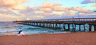 Couple looking into The Sea with Dramatic Clouds at Sunset with Pier