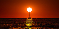 A sailboats mast appears to slice through the setting sun on Lake Michigan
