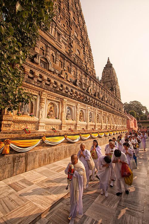 Buddhist pilgrims perform walking meditation around the Mahabodhi Temple, the site of the Buddha's enlightenment,  in Bodhgaya India.