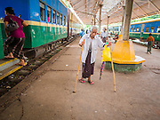 05 JUNE 2014 - YANGON, YANGON REGION, MYANMAR: A man with home made crutches walks through the Yangon train station after arriving of the circular train. The Yangon Circular Train is a commuter train that circles Yangon, Myanmar (Rangoon, Burma). The train is 45 kilometers long, makes 38 stops and takes about three hours to make a loop of the city.     PHOTO BY JACK KURTZ