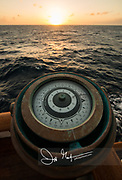 Sunset over the ocean with a gyrocompass, a non-magnetic compass used in sailing, pointing west.