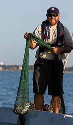 Texas Parks & Wildlife Coastal Fisheries Field Technician, Mark Krupp, holding trawling net containing marine life from Galveston Bay on the Texas Gulf Coast.