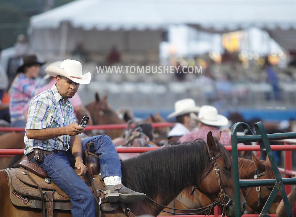 Augusta, New Jersey - A cowboy checks his cell phone while waiting for his turn at the team penning competition at the New Jersey State Fair and Sussex County Farm and Horse Show on Aug. 11, 2010.