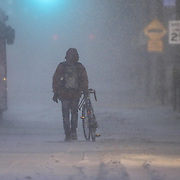 A pedestrian walking his bike down E. Main St. during a storm Friday, Jan, 22, 2016 in Newark.<br /> <br /> A massive blizzard dumps snow in Newark, and eastern United States on Friday, with mass flight cancellations, five states declaring states of emergency.
