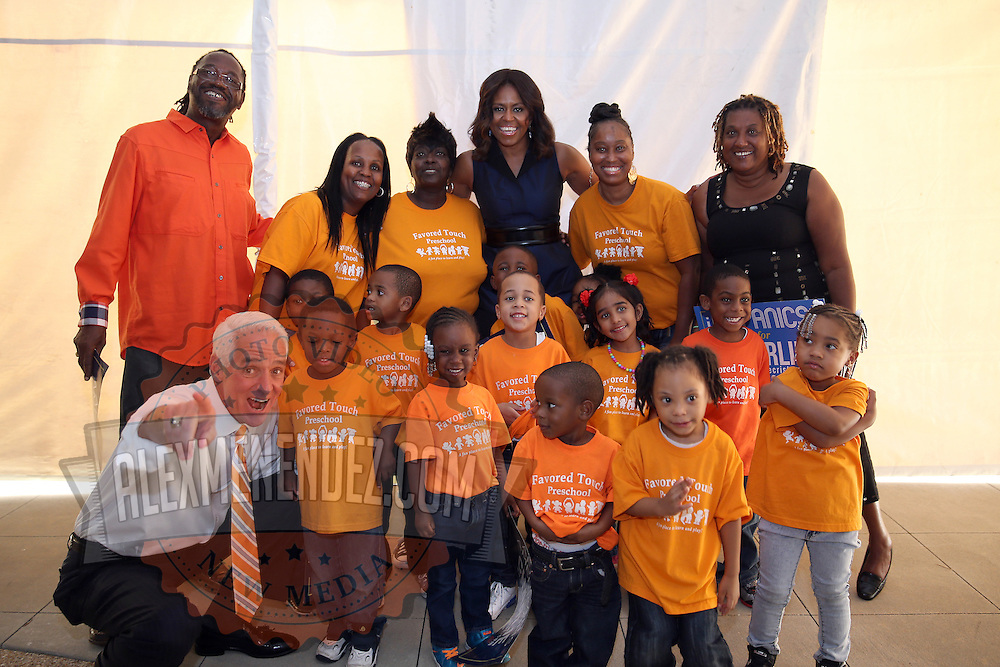 """First Lady Michelle Obama and Charlie Crist pose with children and teachers from the Favored Touch Preschool after the grassroots """"Commit to Vote"""" rally for Democrat at the Barnett Park Gymnasium in Orlando, Florida on Friday, Nov. 17, 2014. (AP Photo/Alex Menendez)"""