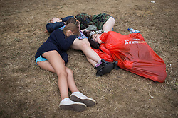 © Licensed to London News Pictures . 20/07/2013 . Suffolk , UK . Four girls lie asleep on the ground in a huddle . The Latitude music and culture festival in Henham Park , Southwold . Photo credit : Joel Goodman/LNP