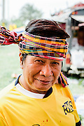 Man wearing Pa Kow Ma traditional scarf at temple fair outside of Kumphawapi village, Udon Thani