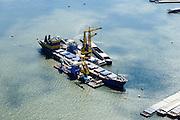 Nederland, Zuid-Holland, Rotterdam, 10-06-2015;  Marcor stuwadoors in Waalhaven. Overslag van agri bulk met drijvende grijperkranen van bulkopslag vaartuig naar binnenvaartschepen.<br /> Marcor stevedoring in Waal harbour. Transhipment of agri bulk with floating grab cranes from bulk storage vessel to barges.<br /> <br /> luchtfoto (toeslag op standard tarieven);<br /> aerial photo (additional fee required);<br /> copyright foto/photo Siebe Swart