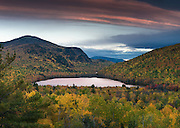 Colorful clouds warm the fall colors surrounding Southbranch Pond at dusk, Baxter State Park, Maine, USA