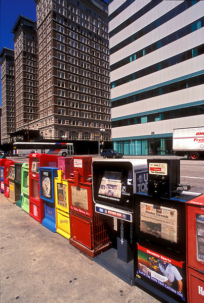 A bank of newspaper vending machines stands against a backdrop of downtown buildings.